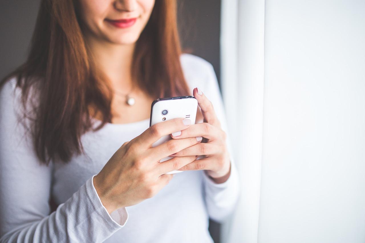 mujer recibiendo mensaje en su móvil