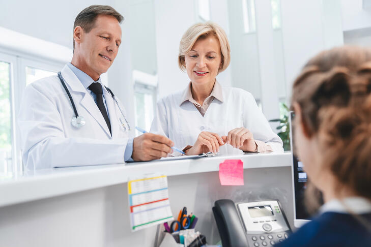 Two-doctors-colleagues-standing-at-reception-desk-talking-and-sharing-information-with-receptionist-in-modern-clinic-1275072738_3867x2579